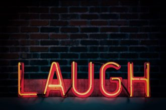 image of neon sign saying laugh